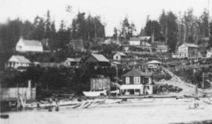 Camano City schoolhouse appears in the distance on the left on the top of the hill.